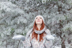 Красивая жизнерадостная счастливая девушка с красными волосами в теплых шляпе и шарфе играя и околпачивая вокруг в снеге в лесе з стоковые изображения