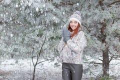 Красивая жизнерадостная счастливая девушка с красными волосами в теплых шляпе и шарфе играя и околпачивая вокруг в снеге в лесе з стоковые фотографии rf