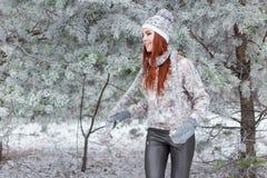Красивая жизнерадостная счастливая девушка с красными волосами в теплых шляпе и шарфе играя и околпачивая вокруг в снеге в лесе з стоковая фотография rf
