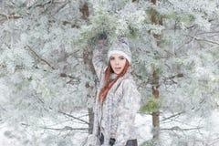 Красивая жизнерадостная счастливая девушка с красными волосами в теплых шляпе и шарфе играя и околпачивая вокруг в снеге в лесе з стоковое изображение rf