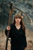 Красивая загадочная мистическая девушка с длинными волосами в черном платье держа оплетку в темном лесе осени на пути Мистическая Стоковые Изображения RF