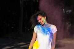 Красивая загоренная женщина представляя с взрывать порошок Holi в стоковая фотография