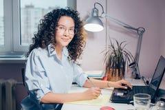 Красивая загоренная женщина при компьтер-книжка представляя к камере Стоковые Фото