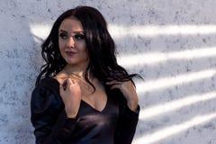 Красивая загоренная модель девушки брюнет стоит против текстурированной стены с нашивками света от шторок стоковое фото