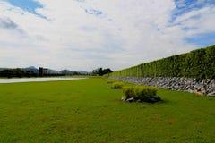Красивая загородка дерева, зеленое поле и камень с голубым небом и clo Стоковое Изображение