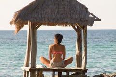 Красивая задняя часть девушки внутри ослабляет на пляже на заходе солнца Стоковая Фотография