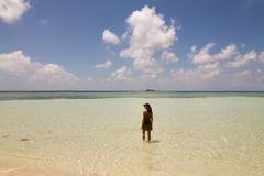 Красивая задняя часть девушки на пляже идя на воду Стоковые Изображения