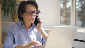 Красивая зрелая коммерсантка говоря на телефоне смотря экран компьтер-книжки дома видеоматериал
