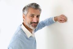 Красивая зрелая склонность человека против стены Стоковая Фотография RF