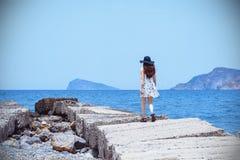 Красивая, изумительная мечтательная девушка, идет вдоль каменной пристани, наслаждаясь порывами ветра ветра, бронзовая кожа, темн Стоковое Изображение