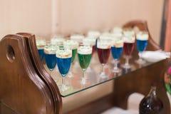 Красивая линия различных покрашенных коктеилей на таблице букета ресторанного обслуживании служила для партии стоковая фотография