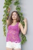 Красивая длинн-с волосами девушка в прозрачное верхнем и представляет против стены листьев плюща Стоковое Изображение