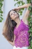 Красивая длинн-с волосами девушка в прозрачное верхнем и представляет против стены листьев плюща Стоковое Изображение RF