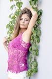 Красивая длинн-с волосами девушка в прозрачное верхнем и представляет против стены листьев плюща Стоковая Фотография RF
