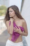 Красивая длинн-с волосами девушка в прозрачное верхнем и представляет против стены Стоковая Фотография RF