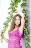 Красивая длинн-с волосами девушка в прозрачное верхнем и представляет против стены листьев плюща Стоковые Фото
