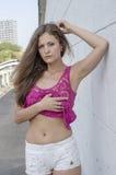 Красивая длинн-с волосами девушка в прозрачное верхнем и представляет против стены Стоковые Изображения RF