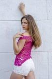 Красивая длинн-с волосами девушка в прозрачное верхнем и представляет против стены Стоковое Фото