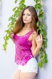 Красивая длинн-с волосами девушка в прозрачное верхнем и представляет против стены листьев плюща Стоковое фото RF