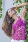 Красивая длинн-с волосами девушка в прозрачное верхнем и представляет против стены листьев плюща Стоковое Фото