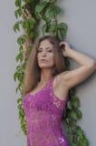Красивая длинн-с волосами девушка в прозрачное верхнем и представляет против стены листьев плюща Стоковые Изображения