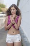 Красивая длинн-с волосами девушка в прозрачное верхнем и представляет против стены листьев плюща Стоковая Фотография