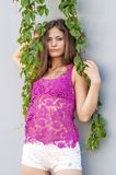 Красивая длинн-с волосами девушка в прозрачное верхнем и представляет против стены листьев плюща Стоковые Фотографии RF