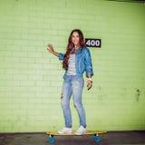 Красивая длинн-с волосами девушка с деревянным скейтбордом около зеленого цвета Стоковые Изображения RF