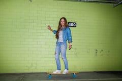 Красивая длинн-с волосами девушка с деревянным скейтбордом около зеленого цвета Стоковая Фотография