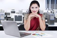Красивая индийская коммерсантка сидя в офисе Стоковые Изображения