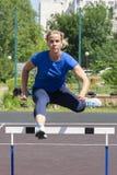 Красивая и атлетическая девушка бежит барьеры в стадионе стоковое изображение rf