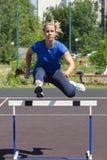 Красивая и атлетическая девушка бежит барьеры в стадионе стоковое фото rf