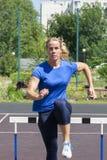 Красивая и атлетическая девушка бежит барьеры в стадионе стоковая фотография