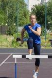 Красивая и атлетическая девушка бежит барьеры в стадионе стоковые фотографии rf