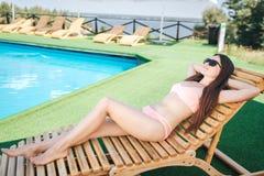 Красивая и изумительная девушка лежит на sunbed и держит руки под головой Она расслаблена солнечные очки девушки носят она стоковое изображение rf