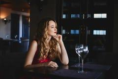 Красивая и модная белокурая модельная девушка с сексуальными красными губами, в красном платье сидит на таблице и представлять в  стоковые фотографии rf