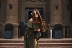 Красивая и модная девушка модели брюнет с очаровательной улыбкой, в стильном платье с нагими плечами и в ультрамодных sunglas стоковые фото