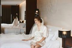 Красивая и модная счастливая невеста с идеальным телом и с вуалью в ее стиле причесок свадьбы сидит на кровати и стоковые фотографии rf