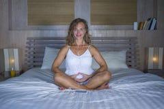 Красивая и подходящая здоровая йога женщины 30s практикуя в кровати сконцентрировала в тренировке раздумья делая форму сердца с е Стоковые Фотографии RF