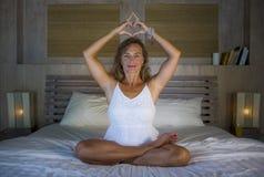 Красивая и подходящая здоровая йога женщины 30s практикуя в кровати сконцентрировала в тренировке раздумья делая форму сердца с е Стоковое Фото