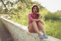 Красивая и привлекательная женщина держа ее руку в ее щеке, сидящ на конкретной стороне, нося сексуальная вскользь джинсовая ткан Стоковые Изображения RF