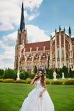 Красивая и сексуальная белокурая модельная девушка, в белом платье и флористическом венке на ее голове, представляет перед церков стоковая фотография