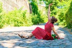 Красивая и сексуальная девушка сидит на дороге кирпича, и букет красных роз лежит сторона - мимо - встает на сторону на поле стоковые фото