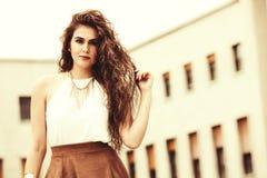 Красивая и уверенно женщина с вьющиеся волосы Урбанский взгляд стоковое изображение