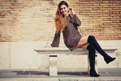 Красивая и усмехаясь молодая женщина сидя на стенде Стоковое фото RF