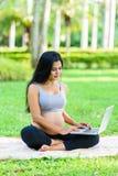 Красивая йога беременной женщины с компьтер-книжкой Стоковые Изображения