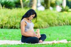 Красивая йога беременной женщины с куклой Стоковая Фотография
