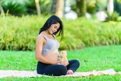 Красивая йога беременной женщины с куклой Стоковые Изображения