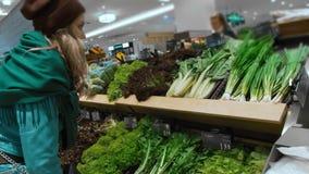 Красивая кавказская девушка в синем пиджаке и зеленом шарфе, выбирает и покупает зеленые овощи и здоровые продукты внутри видеоматериал