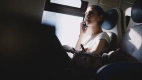 Красивая кавказская девушка усмехаясь, звоня телефонный звонок и смотря вокруг путешествовать самостоятельно на современном сиден акции видеоматериалы